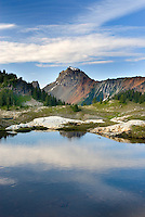 Alpine tarn in basin of Yellow Aster Butte, American Border peak in the distance (2437 meters 7995 feet), Mount Baker Wilderness Washington USA beauty in nature