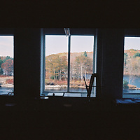 """1. When was this photo taken?<br /> <br /> October 2013<br /> <br /> 2. Where was this photo taken?<br /> <br /> Brunswick, Maine<br /> <br /> 3. Who took this photo?<br /> <br /> A friend<br /> <br /> 4. What are we looking at here?<br /> <br /> """"Artist's Studio Frames the World"""" is the title I would give to this photo. We are standing inside an artist group's rented studio (you see a painter's easel silhouetted by the left-most window, for example), enjoying the view of the Androscoggin River and autumn-colored trees on the sunny nearby island, and also on the farther shore.<br /> <br /> 5. How does this old photo make you feel?<br /> <br /> Happy, contented, and """"lit-up"""".<br /> <br /> 6. Is this what you expected to see?<br /> <br /> It had been so long since this photo was taken that I'd forgotten the scene, until you kindly developed the roll. Thanks!!<br /> <br /> 7. Does this photo bring back any memories?<br /> <br /> Yes, a very pleasant journey through Maine 3 years ago.<br /> <br /> 8. How do you think others will respond to this photo?<br /> <br /> I hope the artists whose studio I visited might enjoy seeing this photo. And I hope your audience appreciates the black """"framing"""" of the three colorful scenes, made additionally interesting by each end window's 18 smaller window-pane-""""framings""""."""