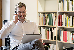 Mid adult businessman using digital tablet and talking on mobile phone in an office, Bavaria, Germany