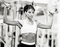 Woman doing lateral curls in gym (B&W, grainy)