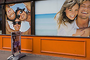 The window of a beauty waxing and tanning salon in central London, features beautiful people with white teeth and tanned caucasian skin.