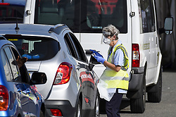 © Licensed to London News Pictures. 17/09/2020. WATFORD, UK.  An NHS worker checks in a car driver ahead of their test at the Covid-19 testing centre outside Watford General Hospital in Hertfordshire.  It is reported that the increased demand for Covid-19 tests has led to local shortages of testing slots and access to community testing has had to be rationed because labs are struggling to keep up with demand.  Photo credit: Stephen Chung/LNP