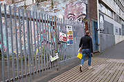 A figure walks past street art graffiti of a face and pair of eyes looking over a fence in Digbeth on 14th March 2020 in Birmingham, United Kingdom. The eyes have a big brother feel of surveillance, as if people nearby are being watched.