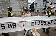 Steelworkers place a beam signed by staff and members of the senior class in position at Yates High School, April 20, 2017.