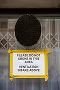 A sign reading 'Please do not smoke in this area, ventilation intake above' appears in the window of the Foreign and Commonwealth Office below a ventilation intake on the 11th of February 2020 in Westminster, London, United Kingdom. Smoking outside offices in London is a common sight.