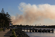The Breakwall Walking Path at Port Macquarie, NSW. Smoke seen from a bush fire.