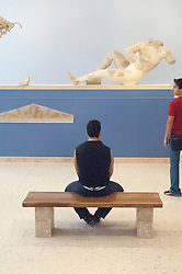 man looking at a sculpture in a museum in Athens, Greece