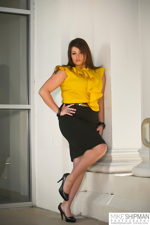 Plus size model wearing a yellow shirt and black skirt