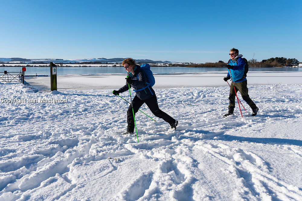 Kinross, Scotland, UK. 11 Feb 2021. Andrew and Rosie Wood from Perth make the most of perfect  cold conditions to go cross-country skiing along the shores of Loch Leven on a sunny cold day with temperature of -7C. Iain Masterton/Alamy Live news