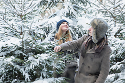 Friends in snowy forest searching a christmas tree, Bavaria, Germany