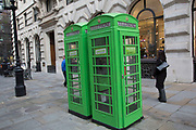 Green Samaritans charity sponsored phone boxes in the City of London, UK. Samaritans is a registered charity aimed at providing emotional support to anyone in distress, struggling to cope, or at risk of suicide throughout the United Kingdom and Ireland, often through their telephone helpline.