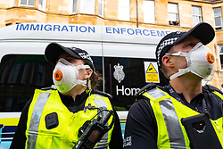 Glasgow, Scotland, UK. 13 May 2021.At approx 5.30 pm police released two men from a Home Office detention vehicle. Accompanied by lawyer Aamer Anwar the men walked to a nearby mosque surrounded by hundreds of police and supporters who had previously been surrounding the vehicle and sitting on the street. Pic; Home Office immigration Enforcement vehicle containing two men is surrounded by protesters. Iain Masterton/Alamy Live News