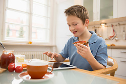 Boy playing with digital tablet at breakfast table