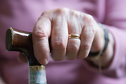 Older woman's hand on a walking stick,
