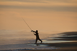 fisherman casting his line into the ocean in East Hampton, NY