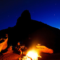Climber relaxes near campfire in Indian Creek, Utah