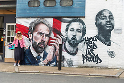 © Licensed to London News Pictures. 14/07/2021. London, UK. A woman poses next to the mural of the England football team including manager GARETH SOUTHGATE and footballers HARY KANE and RAHEEM STIRLING which has been unveiled near London. Bridge. The mural created by Marc Silver of MurWalls, is a celebration of a team that has united the nation. Photo credit: Ray Tang/LNP