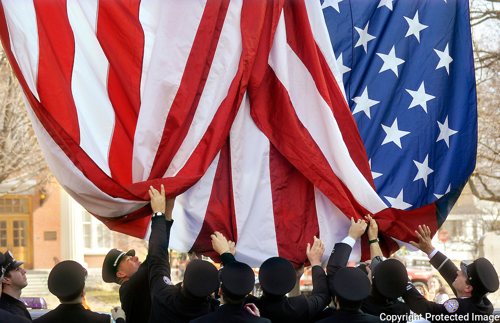 Members of the Rome Fire Department fix a regulation-sized American Flag that they draped from atop a fire engine ladder in honor of the funeral mass for U.S. Marine Lance Cpl. Daniel Geary at St. Peter's Roman Catholic Church in Rome, Saturday, March 28, 2009.