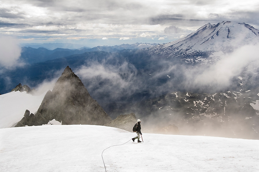 Kevin Steffa leads a climbing team across the Sulphide Glacier below the summit pyramid of Mount Shuksan, North Cascades National Park, Washington. Mount Baker is barely visible in the background.
