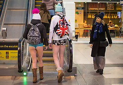 People use the escalator at Liverpool Street station as they take part in No Trousers on the Tube day, in London.