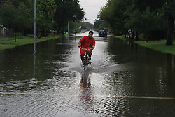 August 27, 2017 Galveston, Texas, U.S. - A man rides bike through flooded street in Galveston. There was at least one death report and several other injuries on Saturday after Hurricane Harvey downgraded to a tropical storm after its strong landfall Friday night. Texas coastal areas, including Houston, have experienced bands of heavy rain and several tornadoes. (Credit Image: © Gaolu/Xinhua via ZUMA Wire)