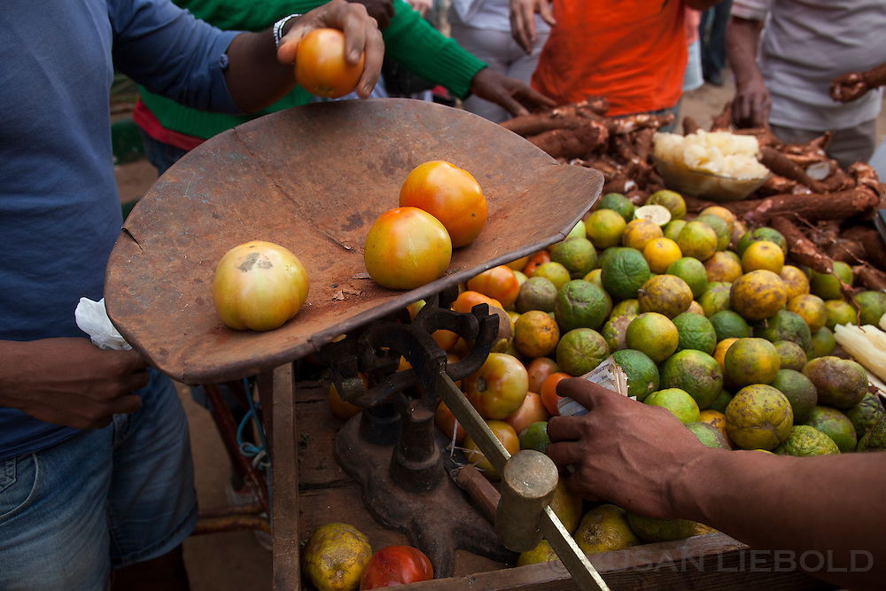 Weighing tomatoes at an outdoor farmers market in Havana, Cuba.