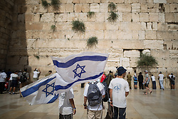 © Licensed to London News Pictures . 05/06/2016 . Jerusalem , Israel . People wave Israeli flags , sing and dance in front of the Western Wall . Israeli Jews celebrate Jerusalem Day . Photo credit : Joel Goodman/LNP