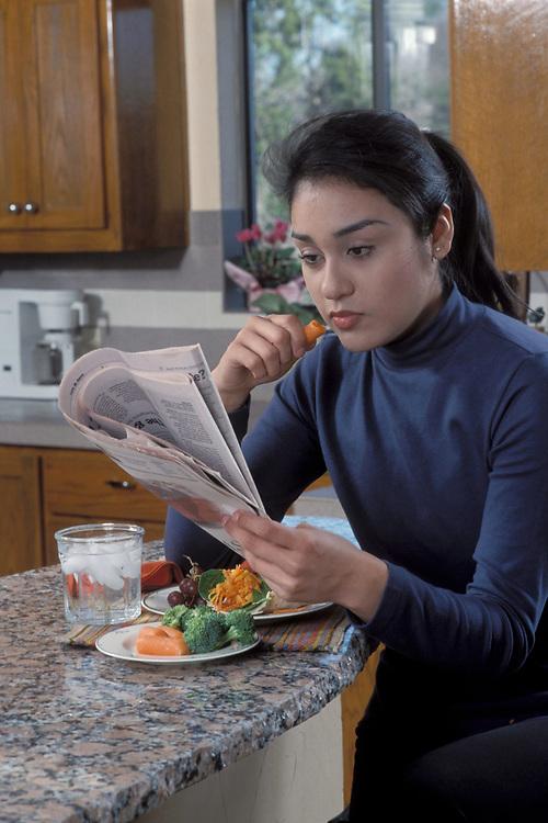 Eighteen year-old Hispanic woman eating healthy food (tortilla wrap) at home.  MR  ©Bob Daemmrich/   CDMM9302
