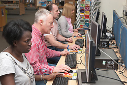 Group of adults using computers in a library.