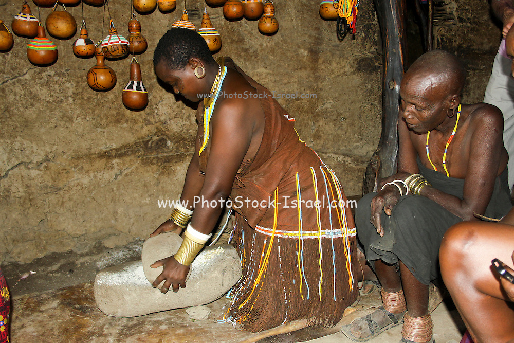 Africa, Tanzania, female member of the Datoga tribe. Woman in traditional dress and beads prepares food for her family, Milling flour
