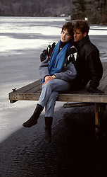 couple sitting on a dock by a frozen lake in Winter