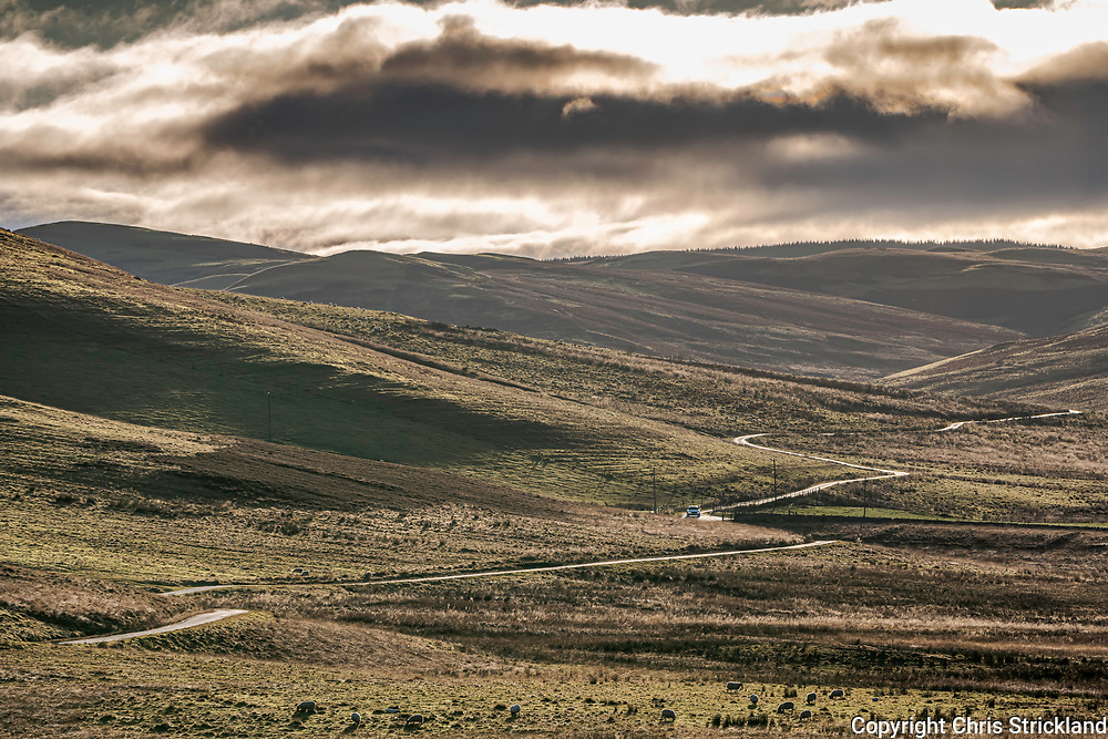 Hownam, Kelso, Scottish Borders, UK. 25th December 2019. A lone car winds it's way through the Kale Valley in the Cheviot Hills.