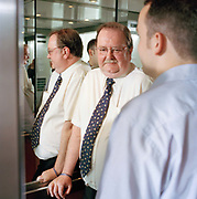 Simon and  Rodger in lift posing for a portrait at his office, in Southampton.  From the series Desk Job, a project which explores globalisation through office life around the World.