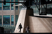 Smokers in a quiet corner of the Broadgate corporate offices development in the City of London. The silhouette of a businessman strides past the two colleagues as one smoker with his back to us, talks to a woman associate, both in a corner, under the tall steel architecture with the backdrop of the Broadgate development within the ancient boundary of the capital's Square Mile, it's financial district founded by the Romans in AD43.
