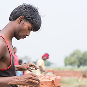 CAPTION: Mason Manjan Kumar carefully ensures his bricks are level as he works on the boundary wall of the OORJAgram Rural Enterprise Zone. LOCATION: Diara Rasulpur, Saran District, Bihar, India. INDIVIDUAL(S) PHOTOGRAPHED: Manjan Kumar.
