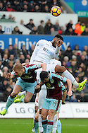 Swansea's Leroy Fer is challenged by Burnley's Ben Mee (l) and Joey Barton (19) for a header. Premier league match, Swansea city v Burnley at the Liberty Stadium in Swansea, South Wales on Saturday 4th March 2017.<br /> pic by  Carl Robertson, Andrew Orchard sports photography.