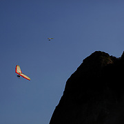 Hang gliders fly past the surrounding hillsides and prepare to land on the beach in the late afternoon light at Sao Conrado beach, Rio de Janeiro,  Brazil. 8th July 2010. Photo Tim Clayton..