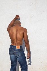 shirtless black man with fist against a wall