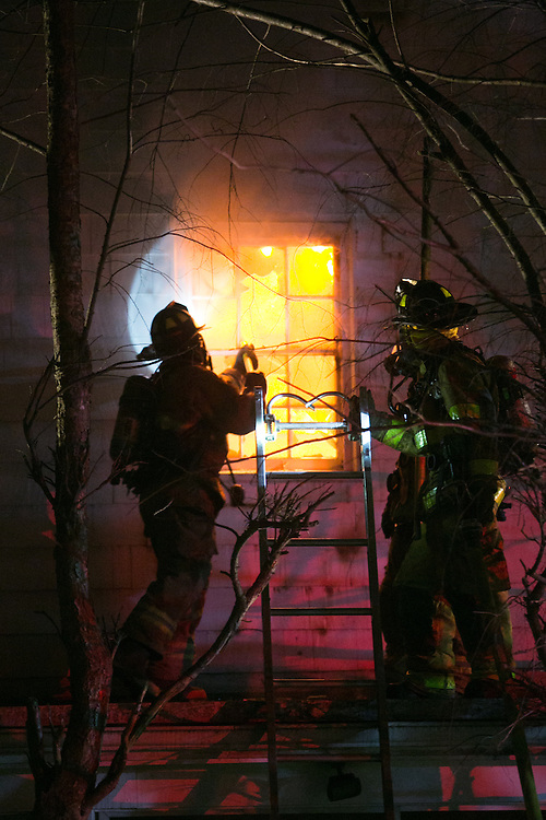 Sherborn, MA 04/11/2013<br /> Firefighters ventilate a window on the 2nd floor of a house at 255 Western Ave. in Sherborn while fighting a 3 alarm fire on Thursday night.<br /> Alex Jones / www.alexjonesphoto.com