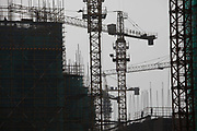 Workers operate on the construction site of the Shouxihu Scenic Garden, a development to house the relocated residents from a lake side area that has been redeveloped as a commercial and tourism spot in Yangzhou, Jiangsu Province, China on 19 July 2012. While the Chinese government has tried various ways to cool down the property market, real estate prices have still seen a steady increase in recent years, proving hard for the country to move away from an investment driven economy.