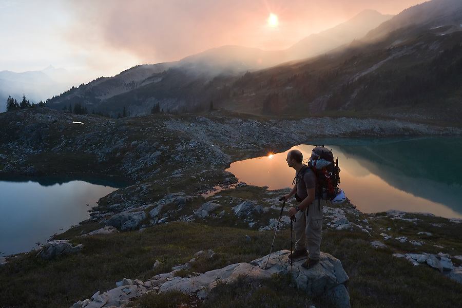 Jim Prager watches as sunlight is turned orange by smoke from a nearby forest fire rising over the beautiful alpine basin at Tapto Lakes, North Cascades National Park, Washington.