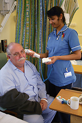 Staff nurse taking patient's temperature using a Tympanic thermometer in the ear,