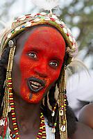 Niger. Gerewol, assemblée générale des Peuls Wadabee d'Afrique de l'ouest. Peul Bororo. Chaque année pendant l'hivernage, les Peul Bororo se retrouvent après un an de transhumances pour célébrer le Gerewol. Profondément animistes, la vie des Bororo est dictée par la beauté. Ce culte atteint son apothéose lors de cette fête originale où seuls les hommes concourent. Après des heures de préparation, ils se présentent en ligne, maquillés, parés de bijoux et de leur plus beaux atours. Ils chantent et dansent lentement ainsi, puis offrent aux femmes leurs sourires crispés et leurs yeux écarquillés afin de mettre en avant l'esthétique de leur visage. Les jeunes filles Bororo se mêlent ensuite aux danseurs et choisissent les plus beaux. // Niger. A Wodaabe-Bororo man with his face painted for the annual Gerewol male beauty contest. Gerewol, general reunion of West Africa for the Wadabee Peuls (Bororo peul). Every year the Peuls are meeting after one year of transhumance to celebrate the Gerewol.