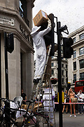 A swarm of bees appear on a set of traffic lights in central London at the junction of Regent Street and Hannover Street. During a busy morning on this well-known street in London's West End, the bees made their presence known above pedestrians by swarming over peoples' heads, which suddenly made their safety all the more, precarious. The beekeepers were called in to deal with the colony and eventually pacified the insects, returning them to a safer environment elsewhere. On-lookers gathered in amazement to witness this natural phenomenon in an urban, manmade location.