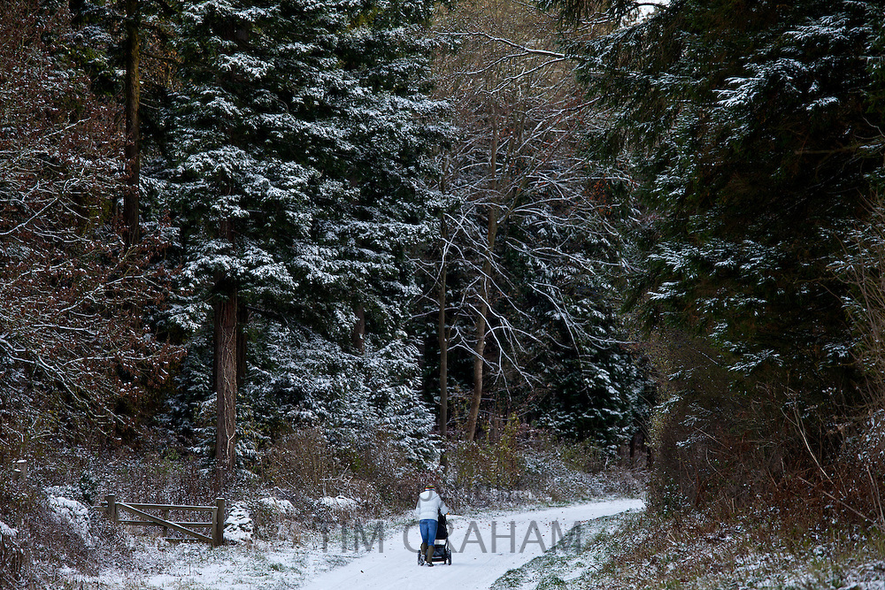 Mother with child in stroller on snowy day in The Cotswolds, UK