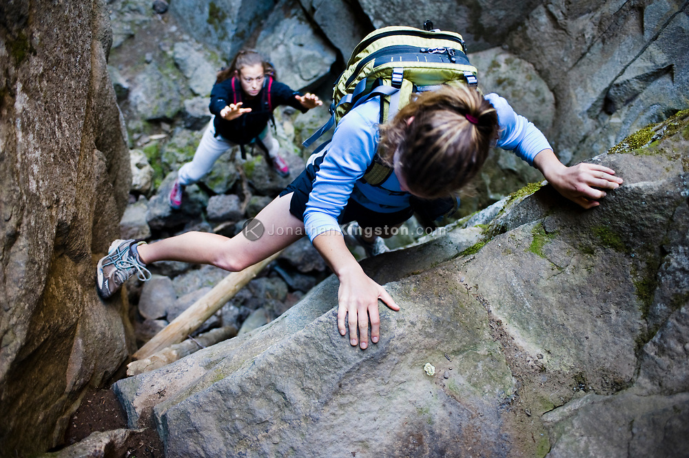 Two women climb through Crack In the Ground, a volcanic fissure near Christmas Valley, Oregon. (Model Released)