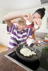 Woman with her son preparing fried eggs in kitchen, Bavaria, Germany