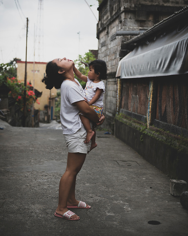 Ubud, Bali, Indonesia - September 19, 2017: Made, age 24, holds her little cousin Kumari outside the home in Ubud.