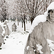 "Statues of soldiers at the Korean War Veterans Memorial covered in fresh snow. The Korean War Veterans Memorial, unveiled in 1992, sits on the northwestern end of the National Mall, not far from the Lincoln Memorial. It consists of several elements designed by different people and groups. It has a triangular footprint with the main elements being ""The Column"" consisting of 19 stainless steel solders, each over 7 feet tall, and a reflective granite wall etched with the faces of thousands of Americans who lost their lives in the war. At one end of the triangle, behind the soldiers, is a grove of trees. At the other is a large American flag and a small Pool of Remembrance. Among the designers were Frank Gaylord (the soldiers) and Louis Nelson (the reflecting granite wall)."