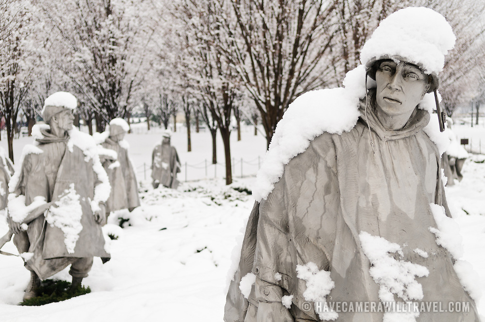 """Statues of soldiers at the Korean War Veterans Memorial covered in fresh snow. The Korean War Veterans Memorial, unveiled in 1992, sits on the northwestern end of the National Mall, not far from the Lincoln Memorial. It consists of several elements designed by different people and groups. It has a triangular footprint with the main elements being """"The Column"""" consisting of 19 stainless steel solders, each over 7 feet tall, and a reflective granite wall etched with the faces of thousands of Americans who lost their lives in the war. At one end of the triangle, behind the soldiers, is a grove of trees. At the other is a large American flag and a small Pool of Remembrance. Among the designers were Frank Gaylord (the soldiers) and Louis Nelson (the reflecting granite wall)."""